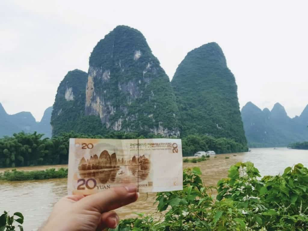 A photo of a 20 Yuan note in front of 20 Yuan note mountain, Yanshuo, guilin mountains, yangshuo mountains,