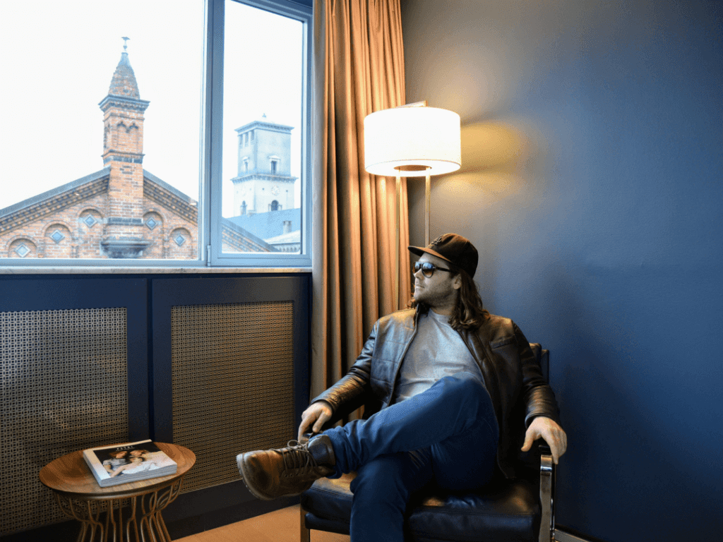 A photo of a man relaxing in the Deluxe Room of Skt Petri Hotel, one of the best 5 star hotels in Copenhagen